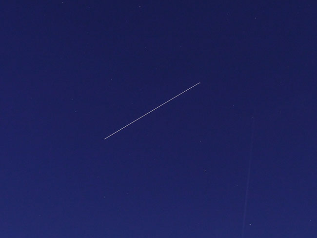 blue sky with iss trail and a few stars