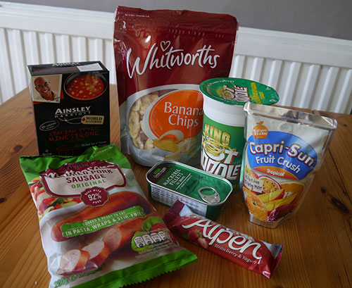 Food on a table - instant soup, banana chips, pot noodle, drink ceral bar, tinned fish, sausage
