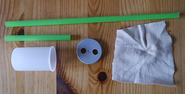 Two straws, a film canister with two holes in the lid, and a piece of cloth